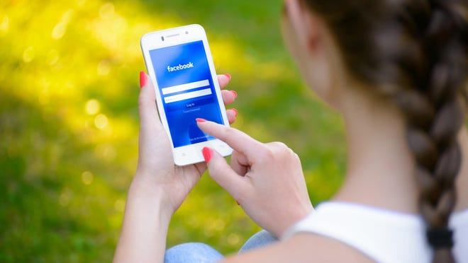 A woman uses the Facebook application on her smartphone. (Maksym Protsenk / Dreamstime)