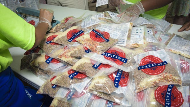 """Prepared meal packages are bagged at a """"Feeding Children Everywhere"""" event."""