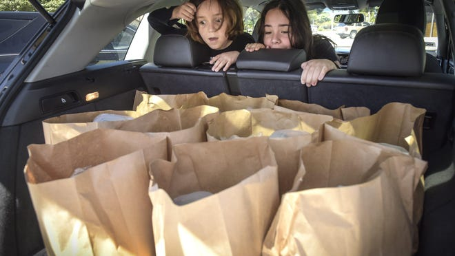 Sebastian Elwell, 6, and his sister Penelope, 9, react to the bags of meals loaded into their car. Penelope is excited to see salad while Sebastian hopes there are cookies. Howley's sets up as a food distribution center, Saturday, March 21, 2020 providing free meals to several local charities, any laid off hospitality worker and of course our Subculture family. Food bags include a roll of toilet paper.