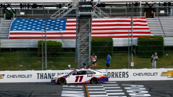 Denny Hamlin gets the checkered flag as he crosses the finish line to win the NASCAR Cup Series auto race at Pocono Raceway, Sunday, June 28, 2020, in Long Pond, Pa.