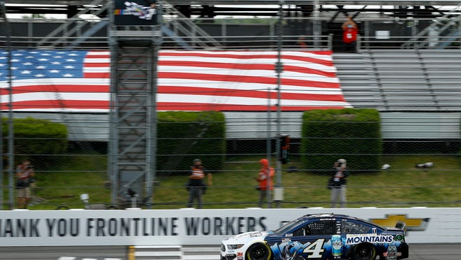 Kevin Harvick takes the checkered flag as he crosses the finish line to win a NASCAR Cup Series auto race at Pocono Raceway, Saturday, June 27, 2020, in Long Pond, Pa.