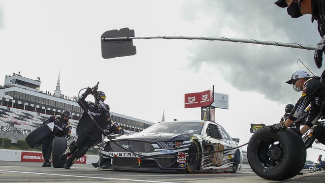 Crew members dash around the car of Aric Almirola as they perform a pit stop during a NASCAR Cup Series auto race at Pocono Raceway, Saturday, June 27, 2020, in Long Pond, Pa.