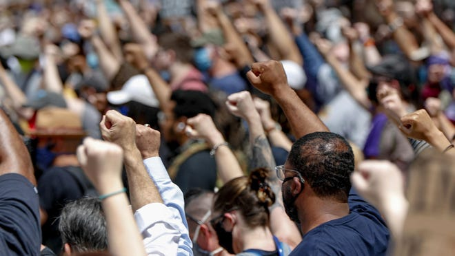 Demonstrators raise fists in the air during a march in Pittsburgh, Saturday, May 30, 2020 to protest the death of George Floyd, who died after being restrained by Minneapolis police officers on Memorial Day, May 25.