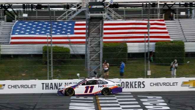 Denny Hamlin gets the checkered flag as he crosses the finish line to win the NASCAR Cup Series auto race at Pocono Raceway, Sunday, June 28, in Long Pond, Pa.