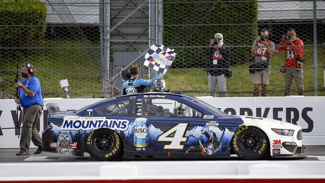 Kevin Harvick waves a checker flag for photographers after winning the NASCAR Cup race Saturday at Pocono Raceway.