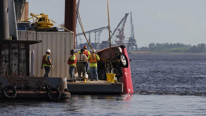 Crane operators work to recover a car Friday that drove into the Cape Fear River early Friday morning , Aug. 28, 2020.