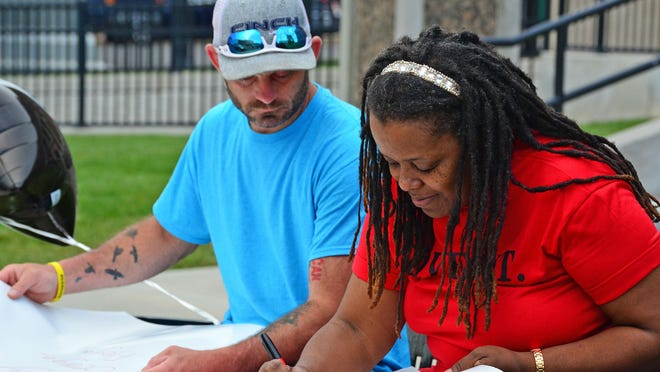 Glenn Higgenbothem and April Williams prepare signs Wednesday recognizing George Floyd prior to a prayer vigil in his honor at the downtown square of Mexico.