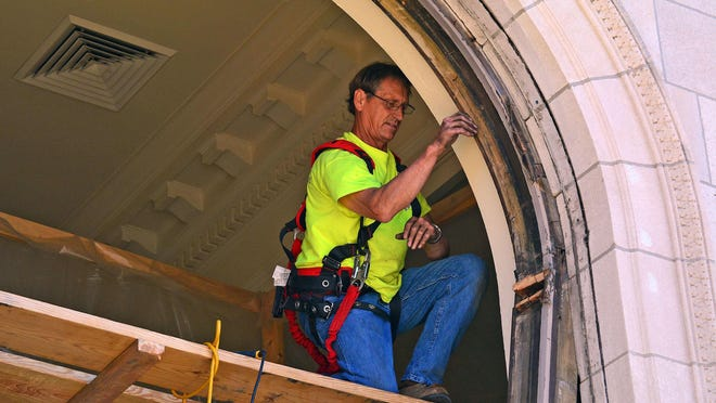 Central Missouri Glass employee Forrest Vestal works to remove the casing Tuesday from one of the large arched windows of the Mexico-Audrain County Library branch in Mexico. The original 102-year-old windows are being restored by Heartland Restoration of Elsberry.