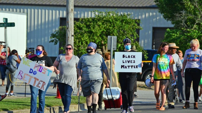 Protestors make their way down Main Street on Friday in Auxvasse. They gathered in front of Auxvasse City Hall to protest the reinstatement of Police Chief Kevin Suedmeyer after posts he made to social media against the ongoing nationwide protests over the death of George Floyd.