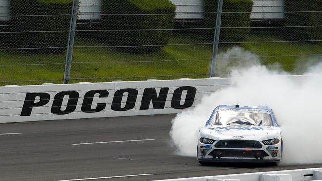 Chase Briscoe smokes his tires in celebration after winning NASCAR's Xfinity Series race at Pocono Raceway on Sunday.