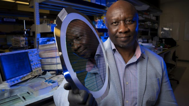 Paul Mola, founder and CEO of Roswell Biotechnologies in Sorrento Valley, Calif., holds up a large silicon chip wafer containing hundreds of thousands of sensors.