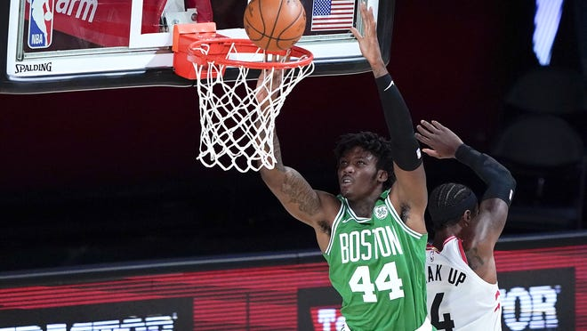 Boston Celtics' Robert Williams III (left) goes up for a basket against Toronto Raptors' Rondae Hollis-Jefferson during the first half of an NBA basketball game on Aug. 7, 2020 in Lake Buena Vista, Fla.
