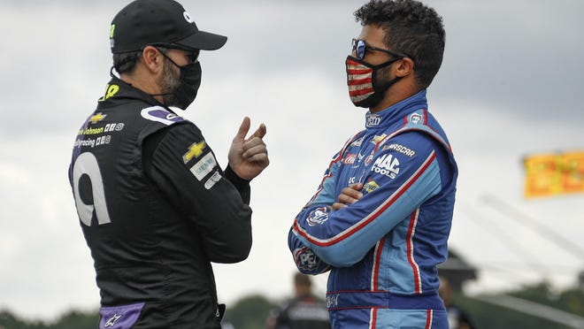 Jimmie Johnson, left, talks with Bubba Wallace before a NASCAR Cup Series race at Pocono Raceway on June 28 in Long Pond, Pa.