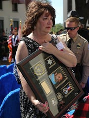 Jill Heddy, holds her husband's photo and memorial