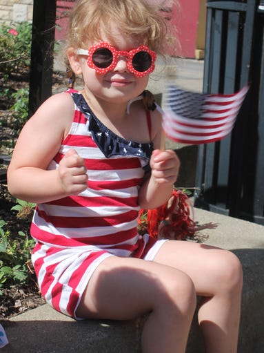 Meadow Daguanno, 3, of Hartland waves her American