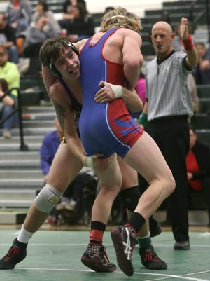 Lexington's Aidan Ammons grabs hold of West Holmes' Josh Baldridge during their 170-pound Ohio Cardinal Conference championship match. Ammons won the title with a 7-3 victory.