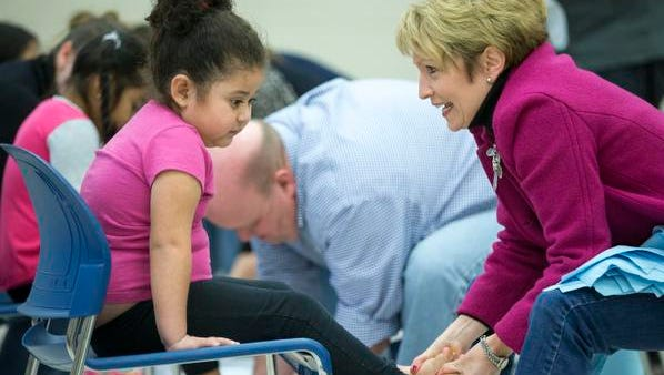 Emily T., a preschooler at Horizon Christian School at Shepherd Academy, gets her feet washed by Lt. Gov. Sue Ellspermann at the Shepherd Community Center in Indianapolis on Friday, Jan. 16, 2016. Afterward, she received new pairs of socks and shoes.