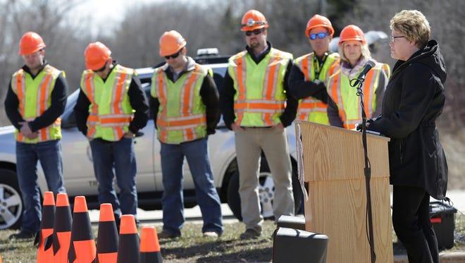 Karen Burkhalter, wife of highway worker Derrick Burkhalter, who was killed in a crash last year in Calumet County, speaks on highway work-zone safety Tuesday in Menasha as highway workers look on.