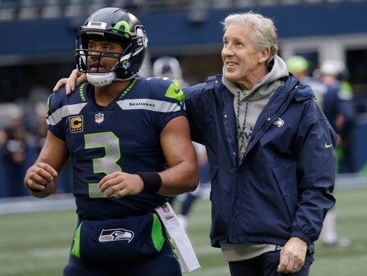 FILE - In this Dec. 17, 2017, file photo, Seattle Seahawks coach Pete Carroll, right, stands with quarterback Russell Wilson before the team's NFL football game against the Los Angeles Rams in Seattle. Carroll was among the top five in voting for the NFL's top coach by an Associated Press panel released Friday, Dec. 29. (AP Photo/Elaine Thompson, File)