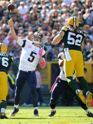 St. Louis Rams quarterback Nick Foles (5) throws as Green Bay Packers linebacker Clay Matthews (52)  is upended by Rams running back Todd Gurley during the first quarter of Sunday's game at Lambeau Field.