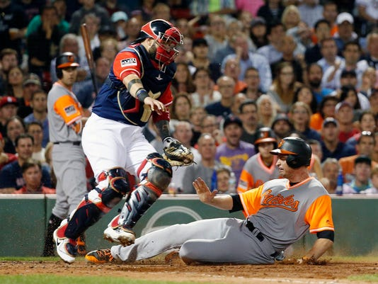 Boston Red Sox's Sandy Leon, left, steps out of the way of Baltimore Orioles' Mark Trumbo on a force at home plate during the fifth inning of a baseball game in Boston, Friday, Aug. 25, 2017. (AP Photo/Michael Dwyer)