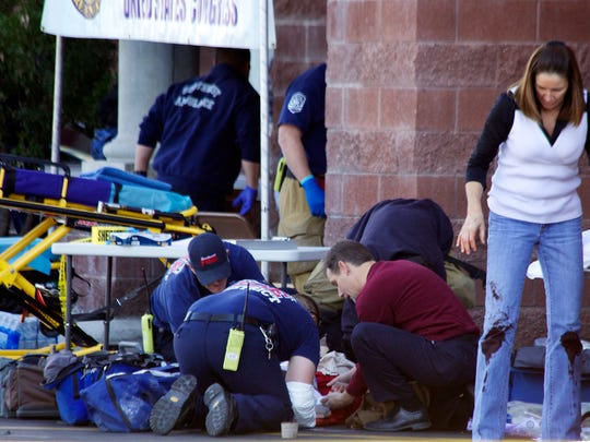 Emergency personnel treat a shooting victim outside a shopping center in Tucson, Ariz., on Jan. 8, 2011, where U.S. Rep. Gabrielle Giffords (D-Ariz.) and others were shot as the congresswoman was meeting with constituents.