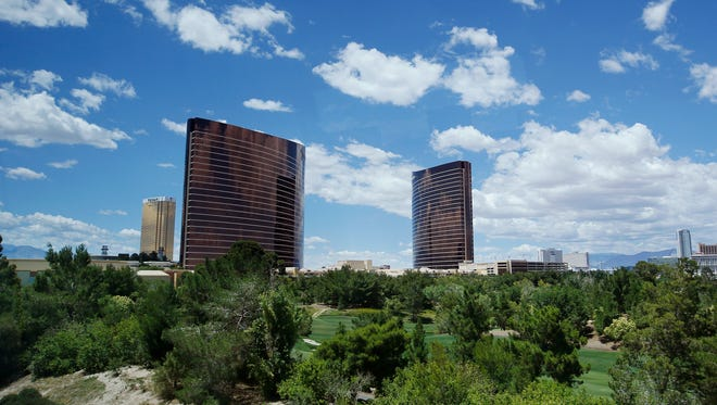 In this May 18, 2016, photo, Wynn and Encore hotel towers rise above the Wynn golf course in Las Vegas. The Paradise Park development proposal unveiled by Wynn Resorts in April is anchored by a 38-acre man-made lake where an 18-hole golf course now sits in Las Vegas. But skepticism about the project's environmental claims includes questions about evaporation, drought and the unethical or unnatural use of water.