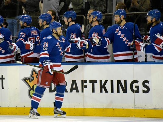 New York Rangers center Derek Stepan (21) celebrates at the bench after scoring during the first period of an NHL hockey game against the Pittsburgh Penguins, Sunday, April 9, 2017, at Madison Square Garden in New York. The Rangers won 3-2. (AP Photo/Bill Kostroun)