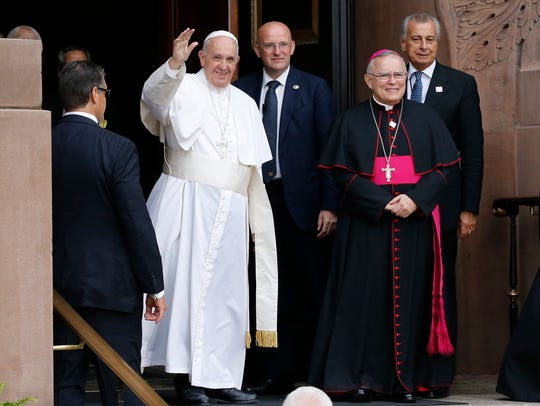 Pope Francis waves as Archbishop Charles Chaput, right,