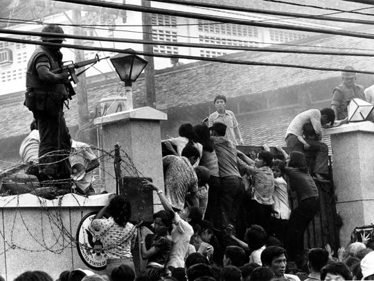 In 1975, mobs of Vietnamese people scale the wall of the U.S. Embassy in Saigon, trying to get to the helicopter pickup zone just before the end of the Vietnam War on April 29, 1975. U.S. Marines and civilians beat them back with their boots and rifle butts.