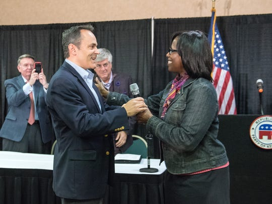 Gov.-elect Matt Bevin receives the microphone from his running mate, Lt. Gov.-elect Jenean M. Hampton, during his introduction to address the Republican State Central Committee Meeting at the Triple Crown Pavilion conference center in Louisville Ky. Nov. 14, 2015