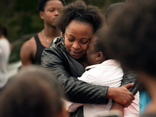 Chantay Skrine, left, comforts Kulonnie Thomas, the oldest sister of William Nash Jr. during a candlelight vigil on Tuesday.
