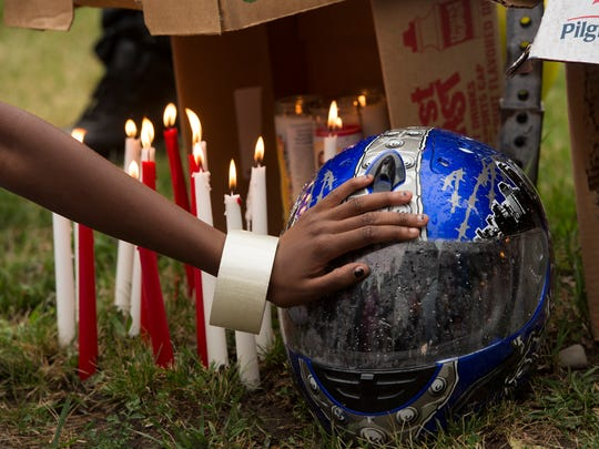 Taliyah McCoy Thomas, 17, holds her hand on the riding helmet of her uncle William Nash Jr., who was fatally struck by a drunk driver while riding his motorcycle on Sunday, during a candlelight vigil in his memory in Binghamton on Tuesday, June 28.