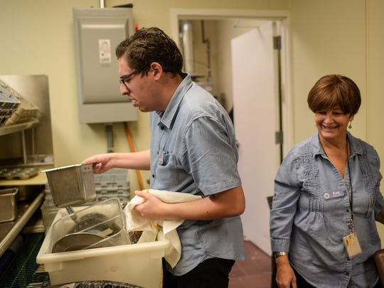 Kim Kaplan (right), trainer of the Friendship Circle, watches David Kole unload dishes at Soul Cafe.
