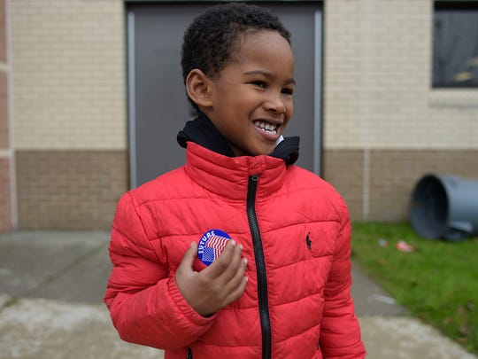 Jacob Allen, 5, poses for a photo with a Future Voter sticker after voting with his mother, Twyla Woolwine, at East Middle School.