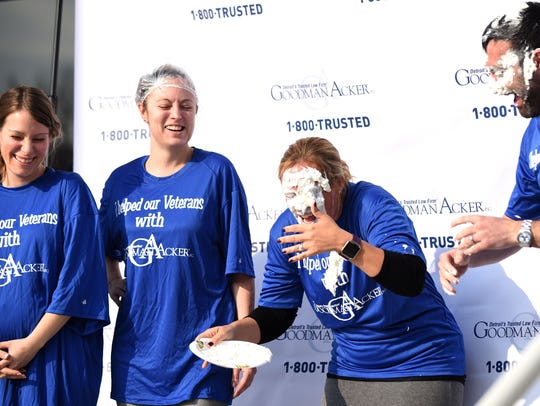 Shana Maitland, center, reacts after taking a pie in