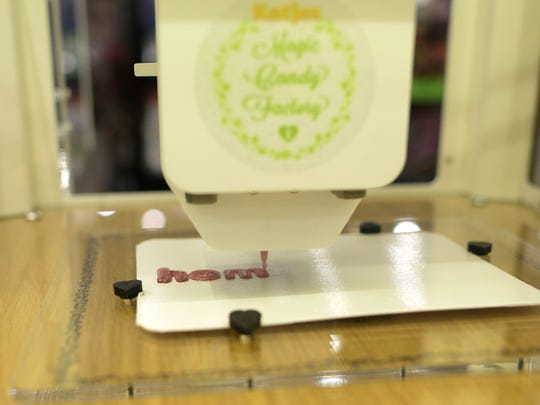 A Katjes Magic Candy Factory 3D printer makes a logo with sublime strawberry flavor gummy candy.