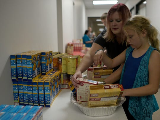 Sossity Morse, 9, and her mother Melissa prepare Thanksgiving baskets.   JUNFU HAN   STAFF PHOTOGRAPHER