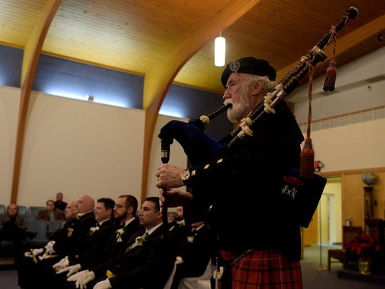 A Scottish bagpiper in full kilt dress ushers in the new officers of the Birmingham Masonic Lodge.