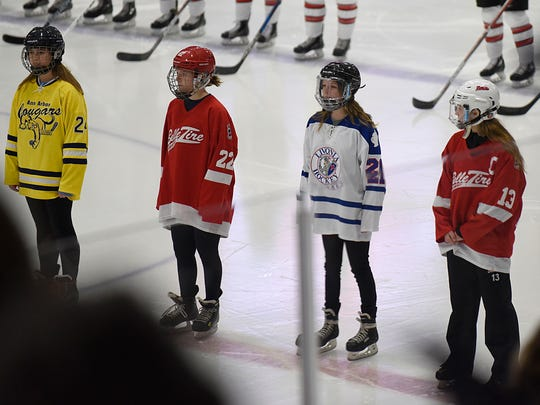 Players from various girls hockey organizations stood at center ice during the Canadian and U.S. national anthems, sung by Northville senior Carly Bins.