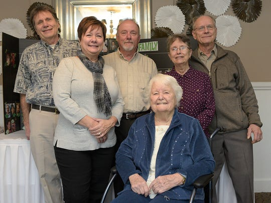 Ruth Sprague poses for a photo Friday with five of