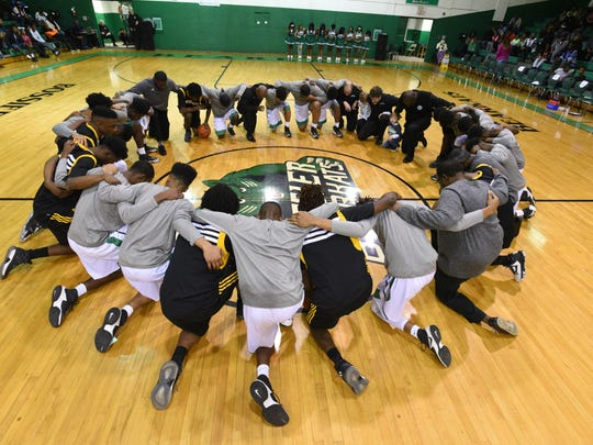 Fair Park and Bossier players pray before the start of their game at the Bossier Invitational boys basketball tournament championship game.