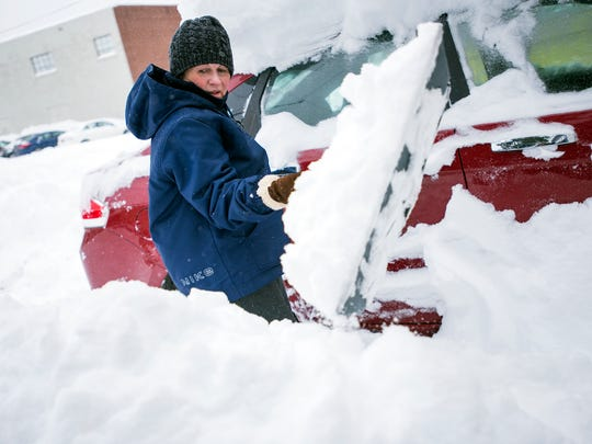 Sheryl Howell shovels out her car in the driveway of her home on Madison Avenue in Endicott on Wednesday, March 15, 2017.