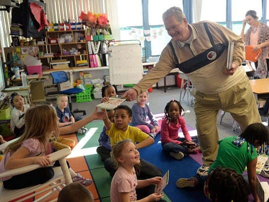 Wayne Lodge member John Bradley gives a book to a first-grader