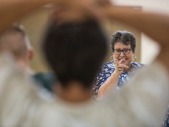 Counselor Lori Huston talks with inmates who have volunteered