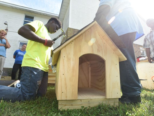 Malik Taylor, 13, of Salisbury puts shingles on the roof of one of the dog houses during The Young Lions Dog House build at Trinity Tabernacle Church and Comminity Center in Salisbury Sunday, Sept. 17, 2017. The youth group sponsored by Labyrinth 807 Masonic Lodge of Salisbury, were on their way to building 15 dog houses with donated material by Lowe's of Salisbury and The Roofing Center. (Photo by Todd Dudek for The Daily Times)
