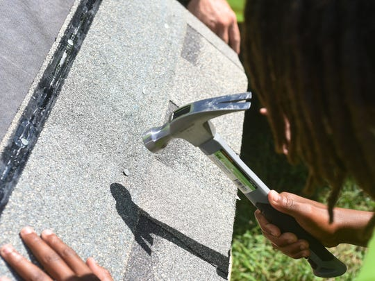 One of the Young Lions hammers a roof shingle in place during The Young Lions Dog House build at Trinity Tabernacle Church and Comminity Center in Salisbury Sunday, Sept. 17, 2017. The youth group sponsored by Labyrinth 807 Masonic Lodge of Salisbury, were on their way to building 15 dog houses with donated material by Lowe's of Salisbury and The Roofing Center. (Photo by Todd Dudek for The Daily Times)
