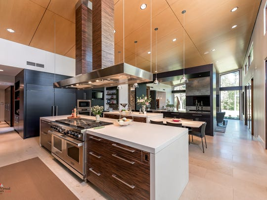 The kitchen has a custom fabricated hood and African Hardwoods are used on the cabinetry with quartz counter tops.