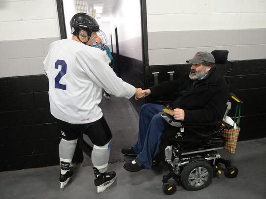 """Father D"" greets players after one of the charity hockey games played in his honor Jan. 15 a the Plymouth Cultural Center."