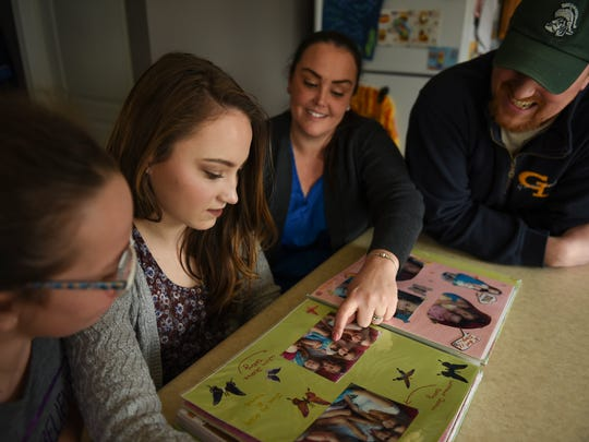 Jacalyn Lambrix, 15,  looks at childhood memory books with her sister Josie, 10, mom Rebecca, and father Brandon at their home in Mulliken Friday, April 6, 2018.  Jacalyn has had two bouts with kidney cancer as a child.  She was diagnosed with Wilm's tumor, a kidney cancer when she was six.  She has been cancer-free for five years.